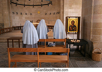 Praying nuns inside The Church of the Multiplication of the...
