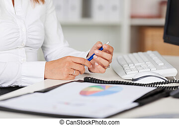 Businesswoman Holding Pen At Office Desk - Midsection of...