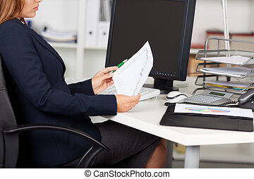 Businesswoman Holding Graph Paper At Desk - Midsection of...