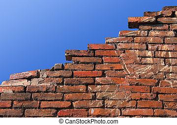 Ruined wall - Old red brick wall against blue sky.