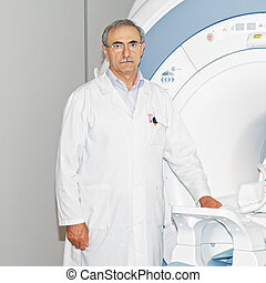Doctor standing at tomograph used for Magnetic Resonance...