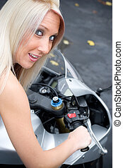 Girl On A Motorcycle - A young blonde woman poses on her...
