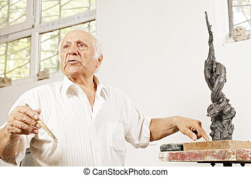 Senior sculptor describing his sculpture in workshop low...