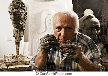 Sculptor in studio - Elderly sculptor in studio holding...