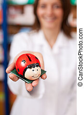 Pharmacist Holding Ladybird Shaped Coinbank - Female...