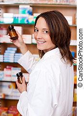 Portrait of happy female pharmacist holding medicine bottles...