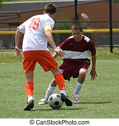 2 soccer players in action - Soccer player trying to beat...