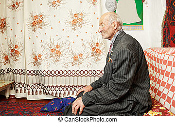 Senior serene man on sofa looking sideways