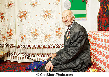 Senior contented man on sofa at home