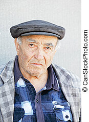 Elderly man in checkered jacket and cap
