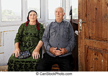 Spouses - Senior spouses sitting at home against big window