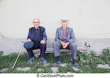 Old friends - Two old friends sitting on bench at wall...