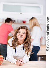 Portrait of happy teenage girl leaning on table with friends working in background