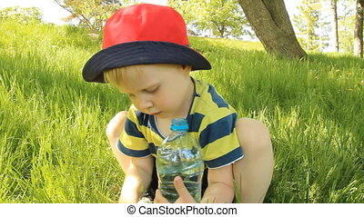 Little boy on the meadow drinking w