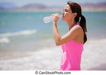 Drinking water at the beach - Cute young woman taking a...