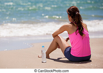Taking a break from running - Young woman in sporty outfit...