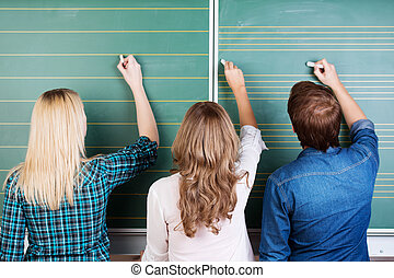 3 Teenage Students Writing On Chalkboard