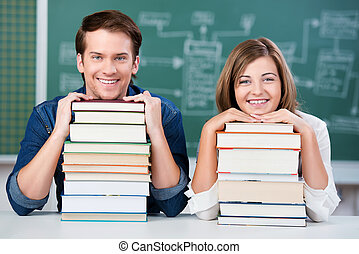 Students Resting Chin On Stack Of Books At Desk - Portrait...