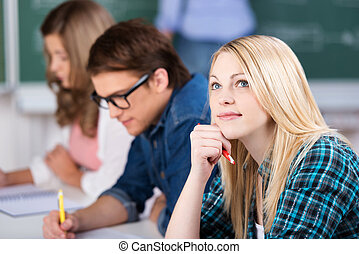 Thinking Female Student Sitting With Classmates - Thoughtful...