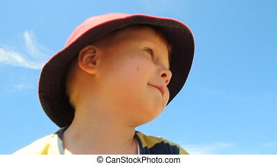 Positive boy with hat smiling and d