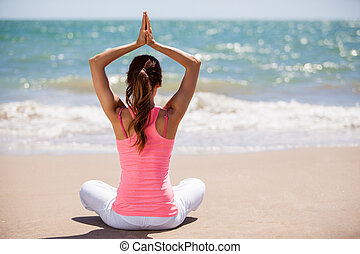 Doing some yoga on a sunny day - Young woman meditating and...