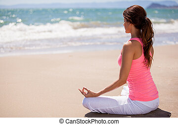 Meditation at the beach - Beautiful young woman doing some...