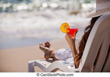 Enjoying a drink by the beach - Closeup of a young woman...