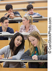 Students learning and talking in a lecture hall - Students...