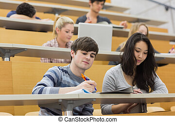 Students listening and taking notes in a lecture hall in...