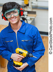 Student standing while holding a driller - Smiling student...