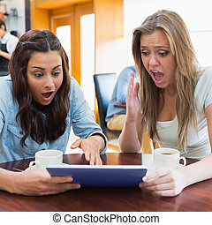 Women looking shocked at tablet pc - Students looking...