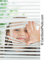 Happy child peeking through blinds - Happy child peeking...