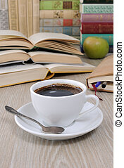 A cup of coffee on a table among books - A cup of coffee on...