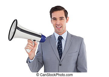 Smiling businessman holding a megaphone on white background