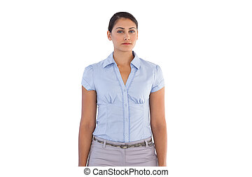 Serious businesswoman standing alone on white background