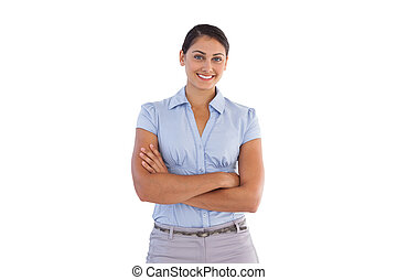 Smiling businesswoman standing alone with her arms crossed