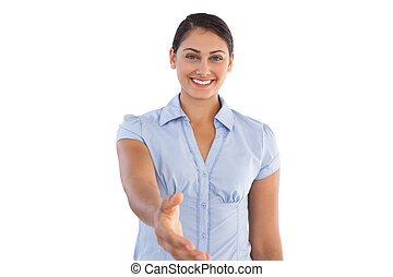 Smiling businesswoman outstretching her hand on white...