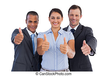 Group of smiling business people showing their thumbs up on...