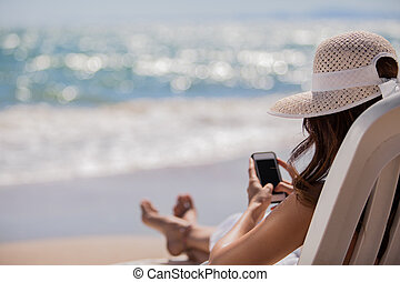 Social networking at the beach - Young woman updating her...