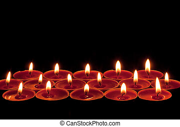 red tea lights - red candlelight edging or border on a black...