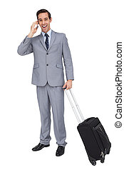 Smiling businessman with his luggage while phoning