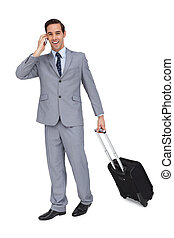 Happy young businessman with his luggage while phoning on...