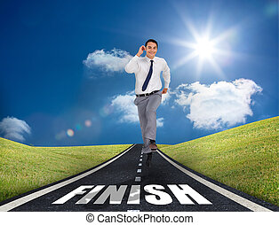 Smiling businessman running on a road