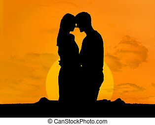 Silhouette of couple embracing under a sunset kneeling face...