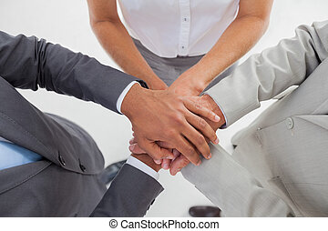 United team piling up their hands in the workplace