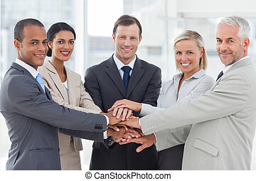 Group of smiling business people piling up their hands...