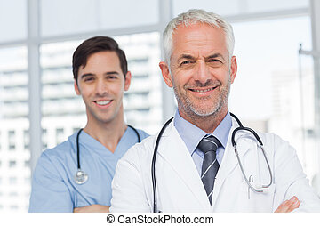 Two smiling doctors standing in front of the camera