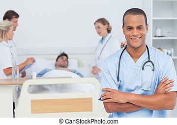 Attractive doctor with arms crossed standing in front of...