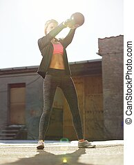 Swinging the Kettlebell Outdoors - Fitness woman during her...