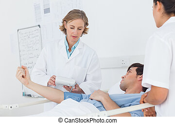 Doctor taking the blood pressure of male patient